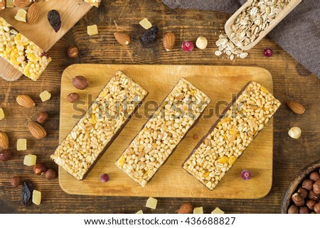 Muesli bars, granola bars on wooden cutting board surrounded with various dried fruits and nuts. Top view. Flat lay food - stock photo