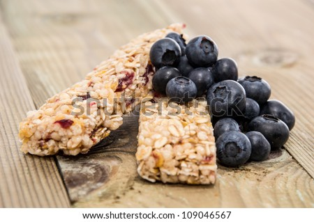 Muesli Bars with fresh Blueberries on wooden background - stock photo
