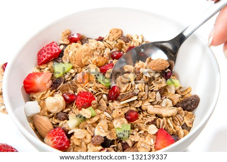 Muesli cereals bowl and spoon with almond, pine nuts, walnut, raisins, oat and wheat flakes, sultanas, fresh fruits kiwi, strawberry pieces, banana, pomegranate seeds - stock photo