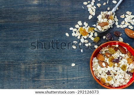Muesli for healthy breakfast over dark wooden background with space for text. Health and diet concept. - stock photo