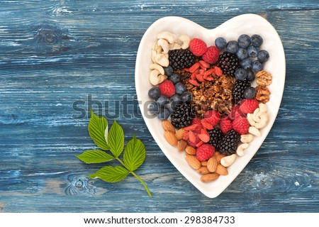 Muesli, goji berries, fresh berries, figs and nuts. Healthy breakfast ingredients. Top view - stock photo