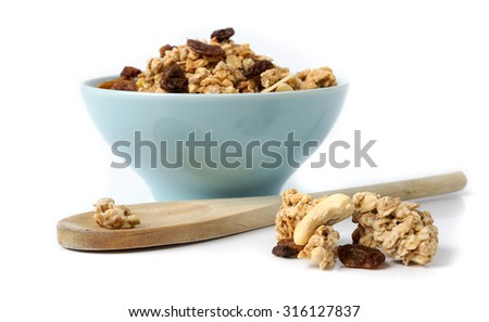 Muesli in bowl and wooden spoon on white background - stock photo