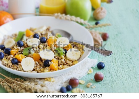 muesli with berries and fruit on a green wooden background. healthy breakfast. selective focus - stock photo