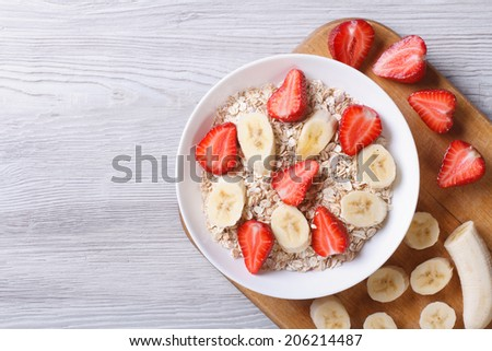 muesli with fresh strawberries and banana with chopped ingredients closeup on wooden background. horizontal top view   - stock photo