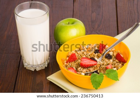 muesli with strawberries and a glass of milk on wooden background - stock photo