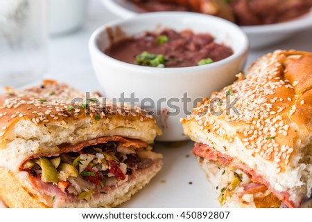 Muffalatta Sandwich with Cup of Red Beans in New Orleans Restaurant - stock photo