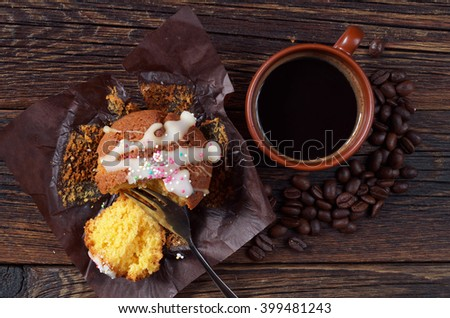 Muffin and slice in brown paper with coffee cup on dark wooden table, top view - stock photo