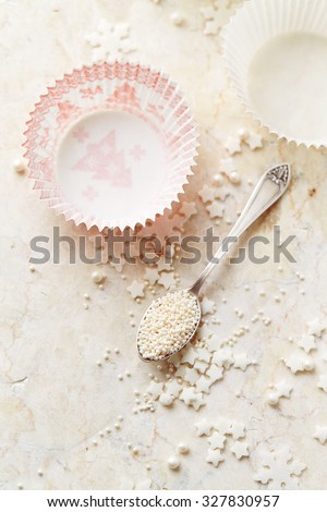 Muffin cases and sugar pearls for Christmas baking - stock photo
