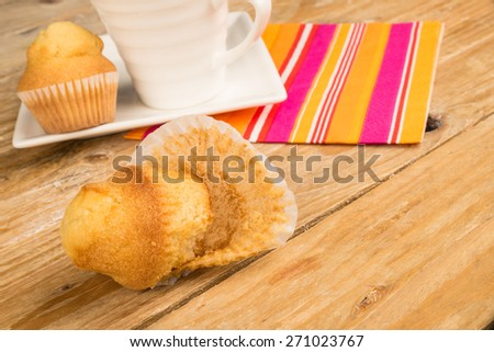Muffin with crumpled paper on a wooden table - stock photo