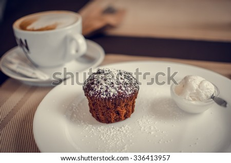 Muffin with ice cream and cup of cappuccino - stock photo