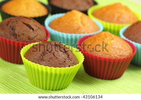 Muffins in colorful silicon moulds on green background - stock photo