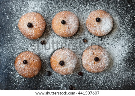 Muffins with black currant sprinkled with powdered sugar. - stock photo