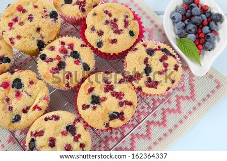 Muffins with cranberries cooling on the grid - stock photo
