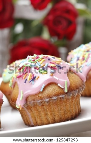 Muffins with pink icing and colorful sprinkles - stock photo