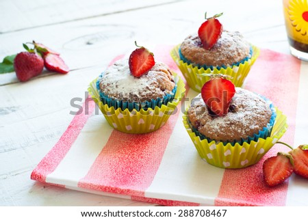 Muffins with strawberries at the clothes - stock photo
