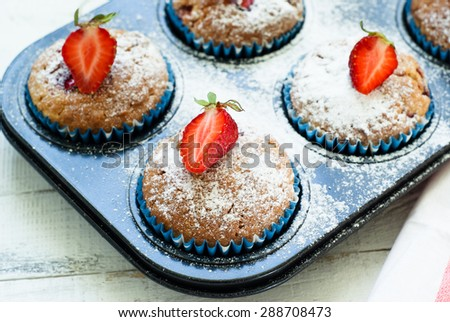 Muffins with strawberries in baking dish - stock photo