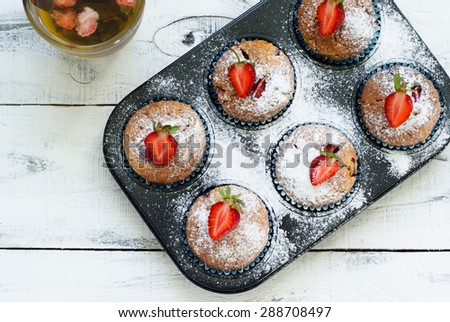 Muffins with strawberries in baking dish. top view - stock photo