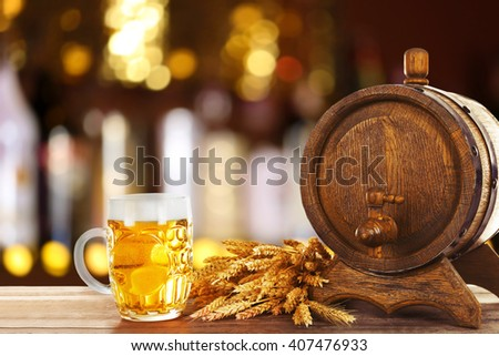 Mug and barrel of cold fresh beer on table, on dark pub background - stock photo