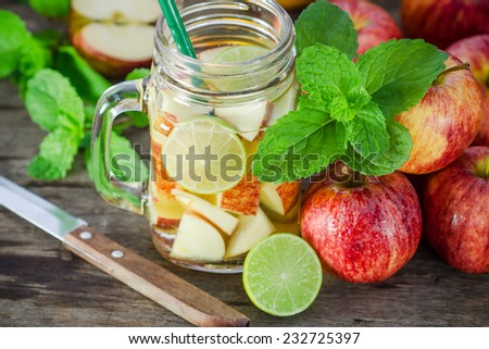 Mug delicious refreshing drink of apple fruits with mint on wooden, infused water - stock photo