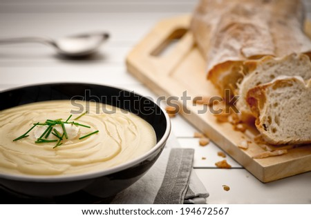 Mug full of fresh homemade potato soup garnished with cream and chives - stock photo