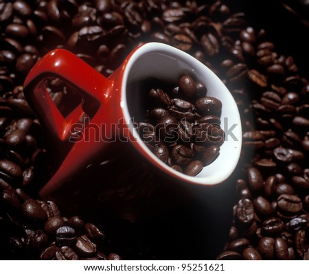Mug in coffee beans - stock photo