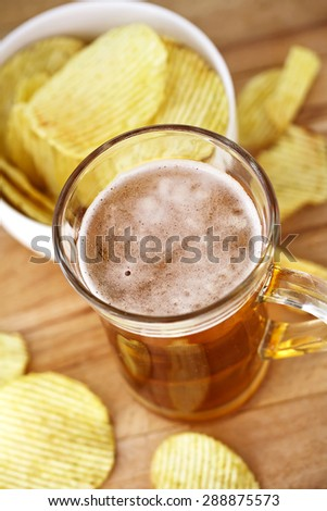 mug of beer and baked potato chips - stock photo
