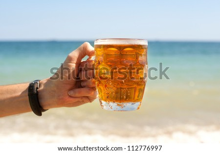 Mug of beer in hand on beach - stock photo