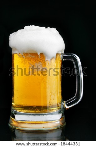 Mug of beer with froth over black background - stock photo