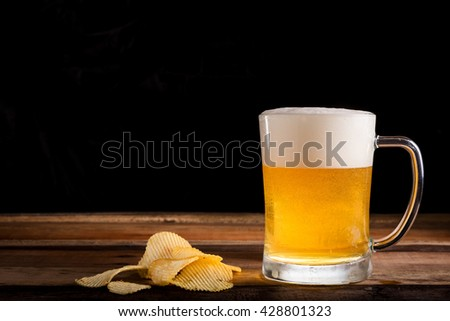Mug of Fresh Beer and  potato chips on wood table on a black background - stock photo