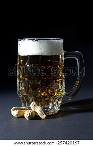 Mug of Fresh Beer with Foam and Peanut in Shell Isolated on Black Background  - stock photo