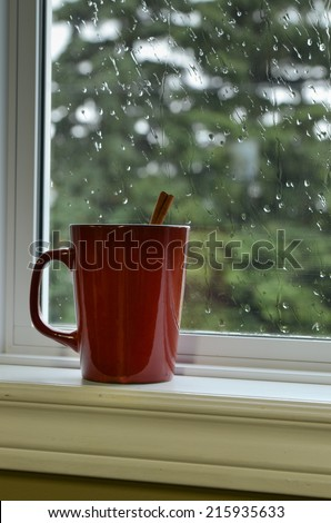 Mug of hot chocolate on a window sill with raindrops on window - stock photo