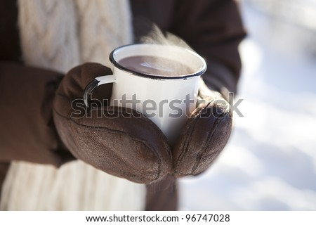 Mug of hot chocolate outdoors on a winter day - stock photo