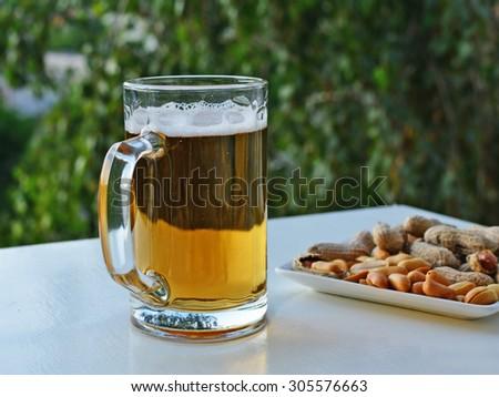 Mug of light beer and peanuts on the backyard table - stock photo