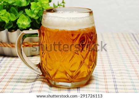 Mug of light beer on a table in the pub or cafe - stock photo