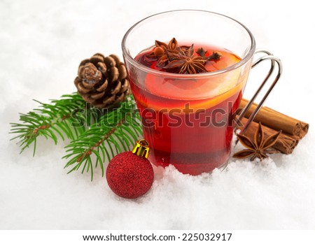 mug of mulled wine and spices in snow - stock photo