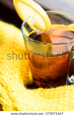 Mug of tea with lemon on a windowsill of a cozy home wrapped in vivid yellow sweater - stock photo