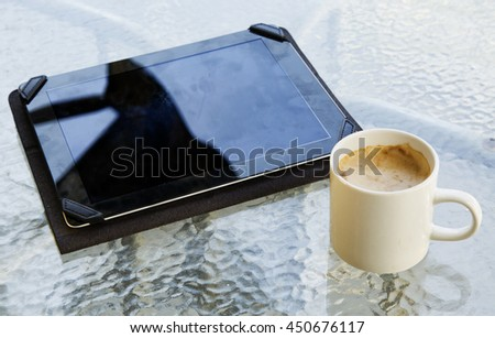 Mug with cappuccino and tablet outside, horizontal image - stock photo