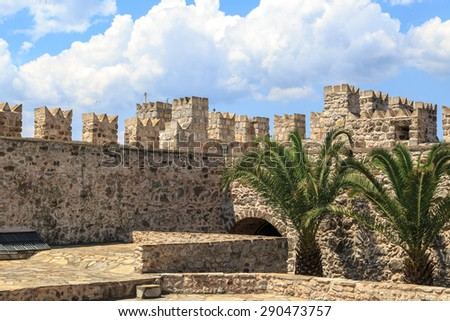 MUGLA, TURKEY - JUNE 1, 2015 : Inside view of high stone walls of historical old Marmaris Tower, on blue sky background. - stock photo