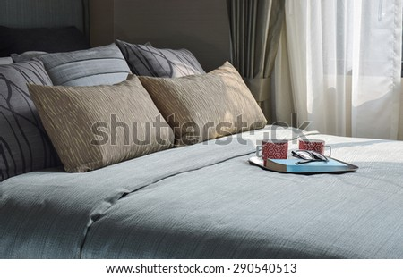 Mugs and book are on the romantic bedding style - stock photo