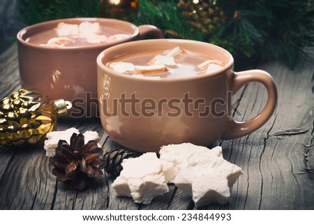 Mugs filled with hot chocolate and marshmallows on old wooden background, Christmas time, vintage style - stock photo