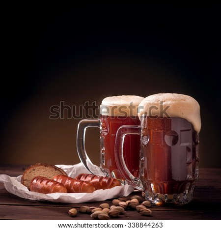 Mugs of beer with snacks on wooden table - stock photo