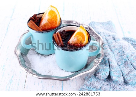 Mugs of mulled wine, piece of orange and spice on metal tray with mittens on color wooden table background - stock photo