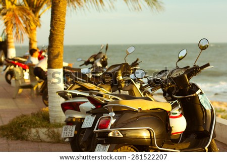 MUI NE, VIETNAM - DECEMBER 30: Scooters parked on parking with sea bay on the city beach during a sunset, City embankment, December 30, 2012, Mui Ne, Vietnam. - stock photo