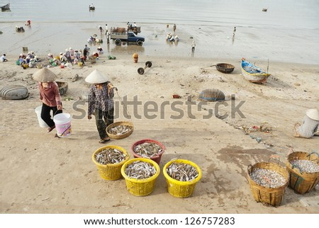 MUI NE, VIETNAM - NOVEMBER 3: Unidentified vietnamese women carry new catch from fishing boats in Mui Ne, Vietnam on November 3, 2008. For most of vietnamese seafood is main source of livelihood. - stock photo