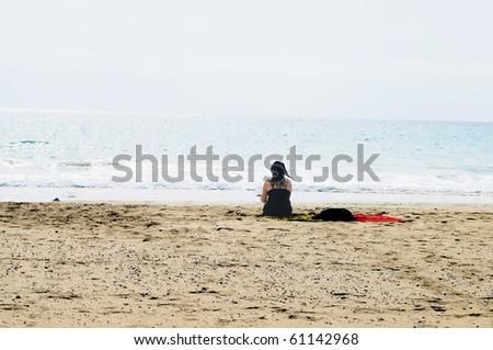 Mujer leyendo en la playa - stock photo