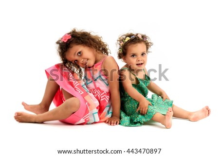 Mulatto sisters are sitting back to back playing. Girls in red and green dress are playing, smiling and showing sister love and happiness. A girl is missing one tooth.  Isolated on white background. - stock photo