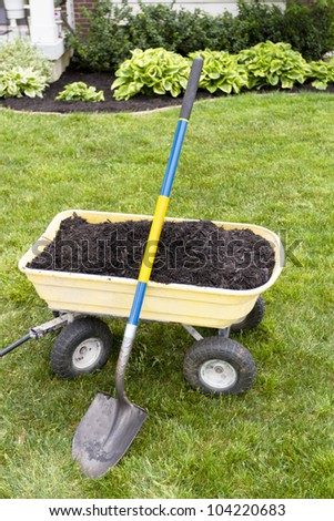 Mulching the around the house with dumping cart and shovel. Nice weekend project. - stock photo