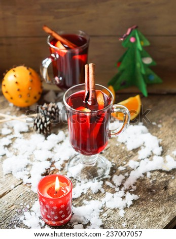 Mulled wine flavored with spices in glass and oranges - stock photo