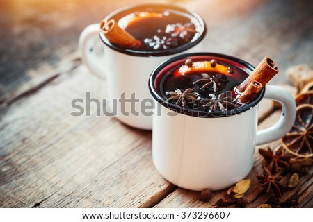 Mulled wine in white rustic mugs with spices and citrus fruit - stock photo