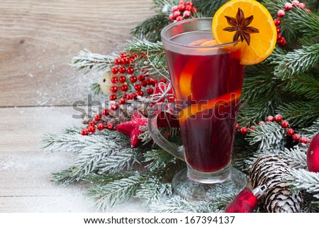 mulled wine with decorated christmas tree in snow  - stock photo